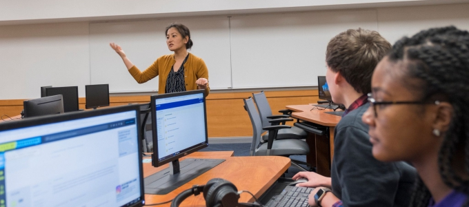 female professor teaching to students looking at computer screen