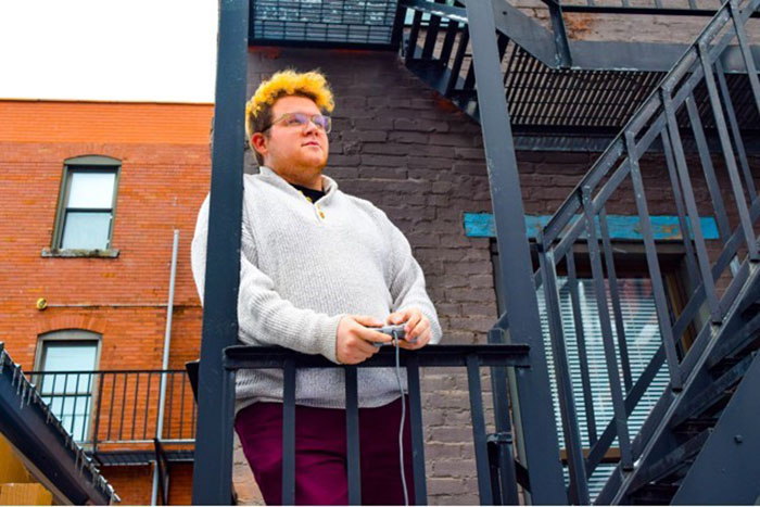 Pat Healy with a device in hand standing on the steps to a building